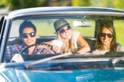 Young adults taking road trip in vintage car.