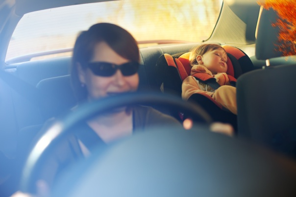 The child in a safety seat near to mother.